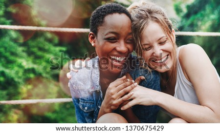 Cheerful girls embracing each other #1370675429