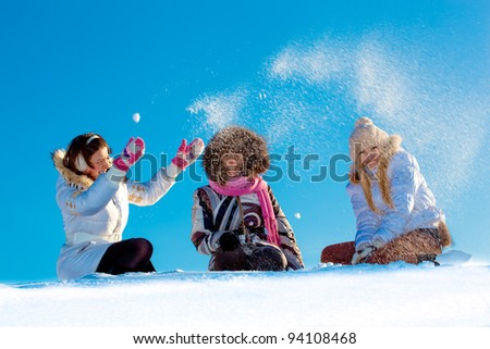 Cheerful girls playing in snowball at blue sky background