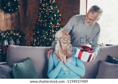 Cheerful glad excited positive adorable beautiful granny sitting on couch divan sofa friend in house receiving getting white gift bow ribbon eve noel box from grey-haired grandpa