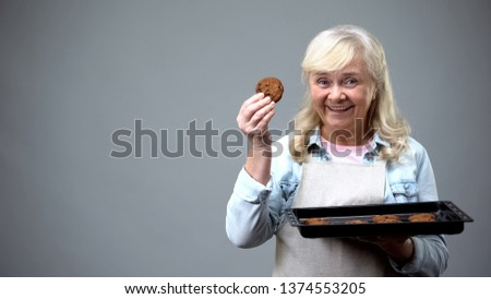Cheerful granny showing chocolate biscuits, cooking school, family traditions