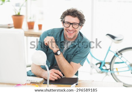 Cheerful graphic designer using a graphics tablet in a modern office