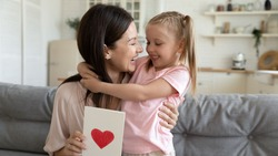 Cheerful grateful young adult mom embracing cute kid daughter holding postcard with red heart, happy parent mum hug little child girl congratulate mommy laughing on mothers day concept sit on sofa