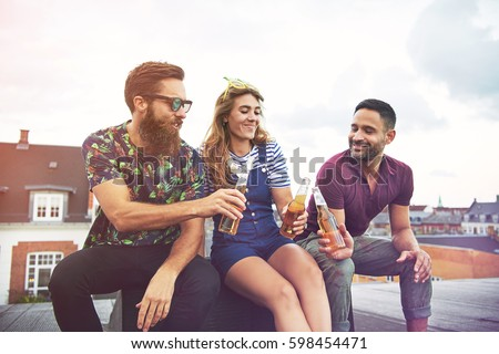 Cheerful group of friendly adults drinking and toasting with beer bottles on roof outdoors with copy space in sky