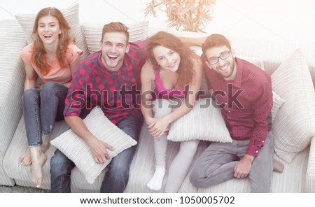 cheerful group of friends laugh ,sitting on the couch. #1050005702