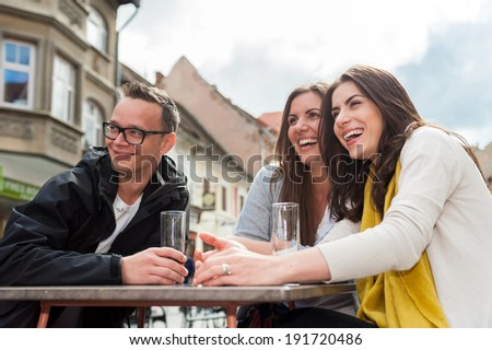 Cheerful group of friends, one man and two women sitting at the table, outdoor cafe shop, reading menu, talking having fun laughing smiling happy. In Brasov city.