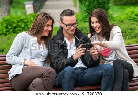 Cheerful group of friends, one man and two women sitting outdoor on a bench in park talking having fun laughing smiling happy watching something on mobile phone .