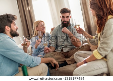 Cheerful  group of  friends sitting on a sofa at home, enjoying conversation and drinking whine. #1318197686