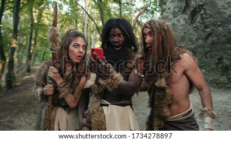 Cheerful group of neanderthal hunters using modern technology smartphone cheering up walking outside cave in the jungle. Technology and first people. Stock photo ©