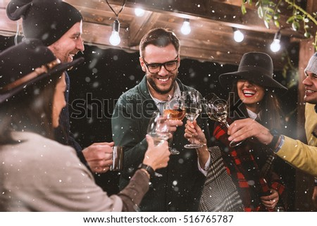Cheerful group of people having fun in the snow, outside the barn at the mountain. Glasses clinking. Winter Concept