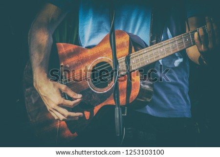 Cheerful guitarist. Cheerful handsome young man playing guitar #1253103100