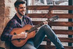 Cheerful guitarist. Cheerful handsome young man playing guitar and smiling while sitting at windowsill