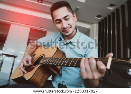 Cheerful guitarist. Cheerful handsome young man playing guitar and smiling while sitting at room, process color #1230317827