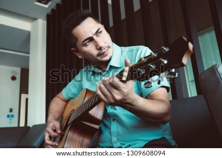 Cheerful guitarist. Cheerful handsome young man playing guitar and smiling while sitting at room, process color #1309608094
