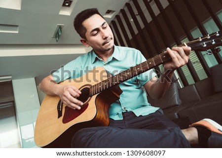 Cheerful guitarist. Cheerful handsome young man playing guitar and smiling while sitting at room, process color #1309608097