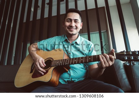 Cheerful guitarist. Cheerful handsome young man playing guitar and smiling while sitting at room, process color #1309608106