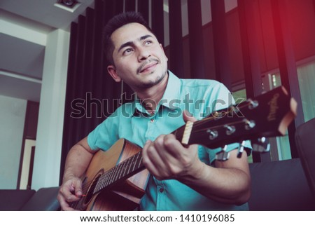 Cheerful guitarist. Cheerful handsome young man playing guitar and smiling while sitting at room, process color #1410196085