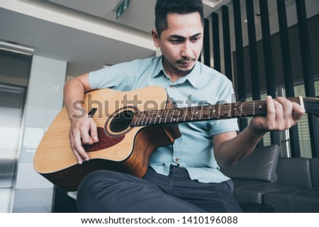 Cheerful guitarist. Cheerful handsome young man playing guitar and smiling while sitting at room, process color #1410196088