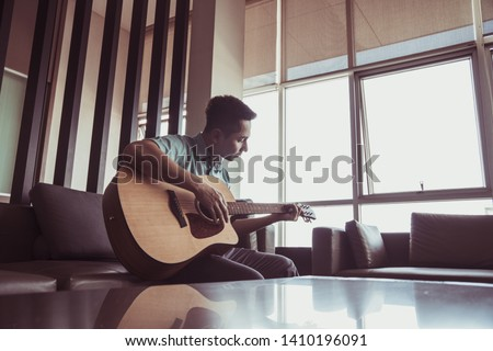 Cheerful guitarist. Cheerful handsome young man playing guitar and smiling while sitting at room, process color #1410196091