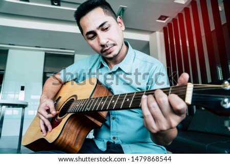 Cheerful guitarist. Cheerful handsome young man playing guitar and smiling while sitting at room, process color #1479868544