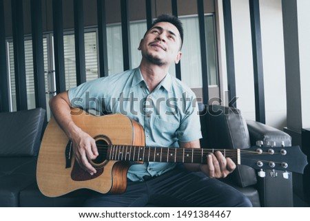 Cheerful guitarist. Cheerful handsome young man playing guitar and smiling while sitting at room, process color #1491384467