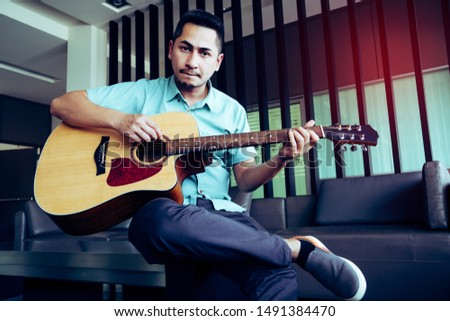 Cheerful guitarist. Cheerful handsome young man playing guitar and smiling while sitting at room, process color #1491384470