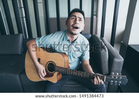 Cheerful guitarist. Cheerful handsome young man playing guitar and smiling while sitting at room, process color #1491384473