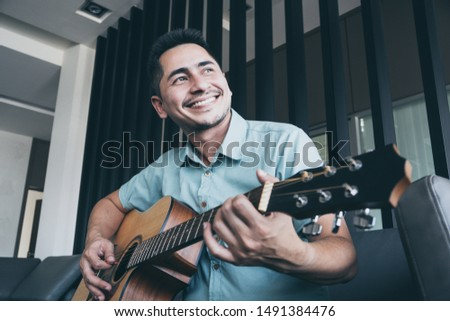 Cheerful guitarist. Cheerful handsome young man playing guitar and smiling while sitting at room, process color #1491384476