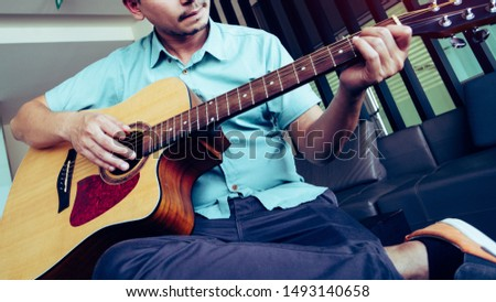 Cheerful guitarist. Cheerful handsome young man playing guitar and smiling while sitting at room, process color #1493140658