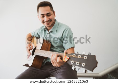 Cheerful guitarist. Cheerful handsome young man playing guitar and smiling while sitting on banister, Vintage color #1268821063