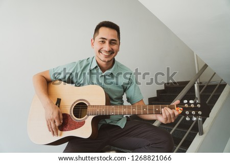 Cheerful guitarist. Cheerful handsome young man playing guitar and smiling while sitting on banister, Vintage color #1268821066