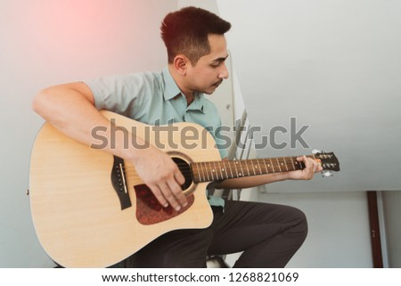 Cheerful guitarist. Cheerful handsome young man playing guitar and smiling while sitting on banister, Vintage color #1268821069