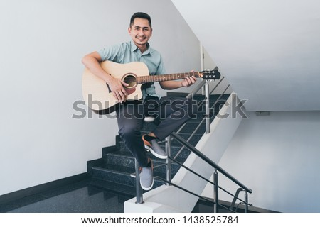 Cheerful guitarist. Cheerful handsome young man playing guitar and smiling while sitting on banister, process color and effect grain. #1438525784
