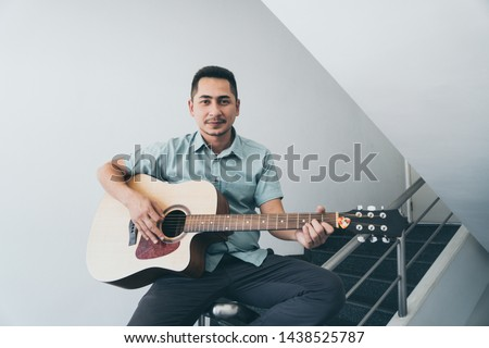 Cheerful guitarist. Cheerful handsome young man playing guitar and smiling while sitting on banister, process color and effect grain. #1438525787