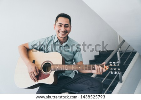 Cheerful guitarist. Cheerful handsome young man playing guitar and smiling while sitting on banister, process color and effect grain. #1438525793