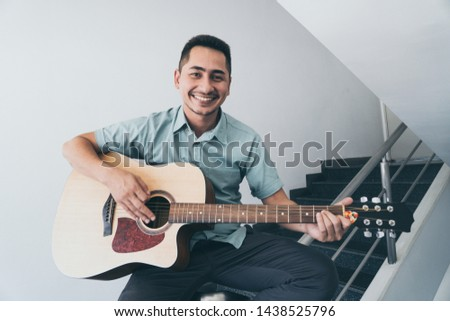 Cheerful guitarist. Cheerful handsome young man playing guitar and smiling while sitting on banister, process color and effect grain. #1438525796