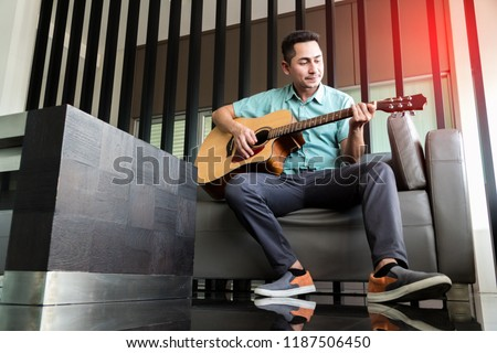 Cheerful guitarist. Cheerful handsome young man playing guitar and smiling while sitting on sofa at room #1187506450