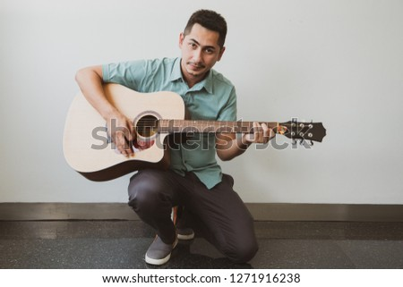 Cheerful guitarist. Cheerful handsome young man playing guitar and smiling while sitting on white wall background. #1271916238