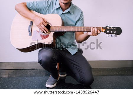 Cheerful guitarist. Cheerful handsome young man playing guitar and smiling while sitting on white wall background. #1438526447