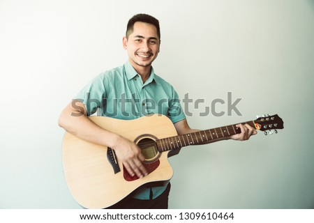 Cheerful guitarist. Cheerful handsome young man playing guitar and smiling while standing on white wall background, process color #1309610464