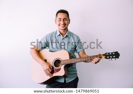 Cheerful guitarist. Cheerful handsome young man playing guitar and smiling while standing on white wall background. #1479869051