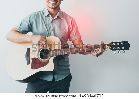 Cheerful guitarist. Cheerful handsome young man playing guitar and smiling while standing on white wall background, process color. #1493140703