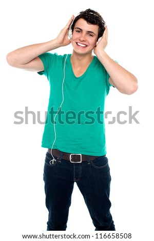 Cheerful guy enjoying loud music holding them tightly to ears