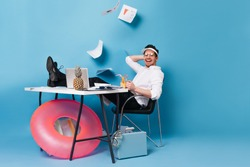 Cheerful guy in white shirt and black pants is working on vacation. Man in cap enjoys cocktail on blue background with falling documents, inflatable circle and suitcase