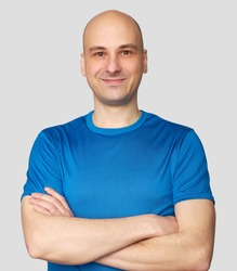 Cheerful guy smiles happily. Confident bald man dresssed casually with arms folded. Isolated over gray studio background