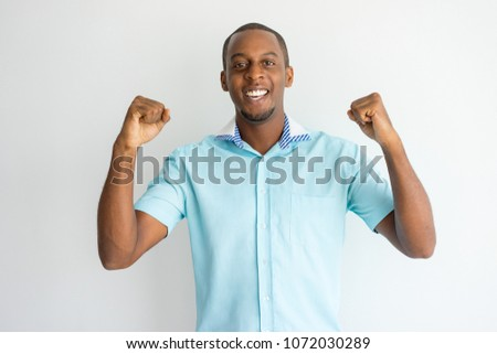 Cheerful handsome African guy in short sleeve shirt making yes gesture while excited about winning. Ecstatic young fan rooting and expressing support. Success concept