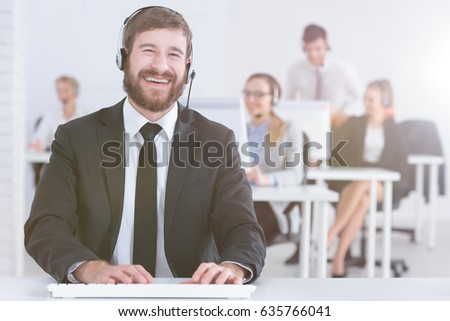 Cheerful handsome call center man with team in background
