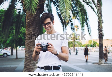 Photo of Cheerful handsome male traveler holding camera satisfied with picture of city destination explore historical places, smiling hipster guy enjoying spending weekends free time on hobby taking photos