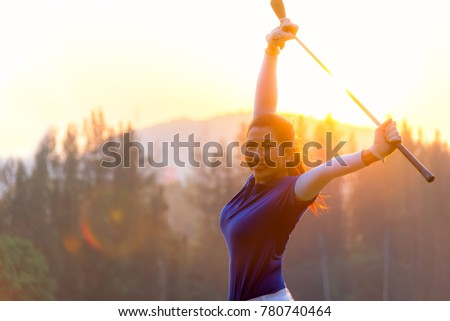Cheerful happy asian smiling woman with a golf in the golf club in the sunny and evening sunset time, copy space.  Lifestyle Concept. - Shutterstock ID 780740464