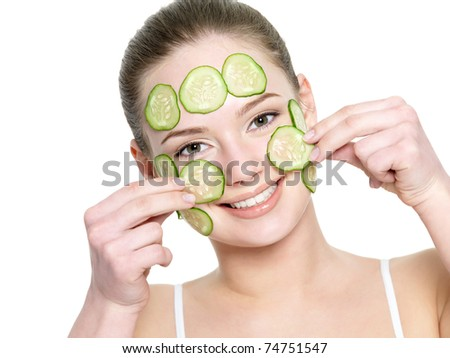 Cheerful happy beautiful girl applying facial mask of cucumber - isolated on white