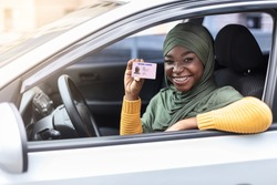 Cheerful happy black muslim woman in hijab sitting in her car and showing new driver license, celebrating driving school finish, passed exam, bought car, sitting inside of vehicle, looking from window